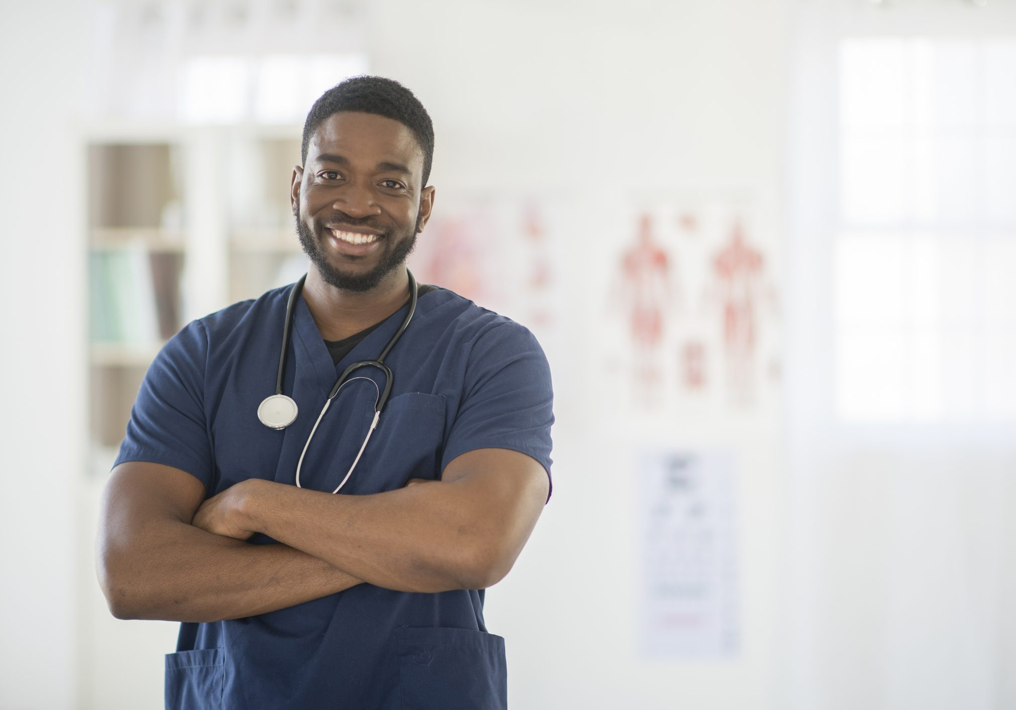 A male nurse is standing in the doctor's office wearing scrubs and a stethoscope. He is smiling and looking at the camera.
