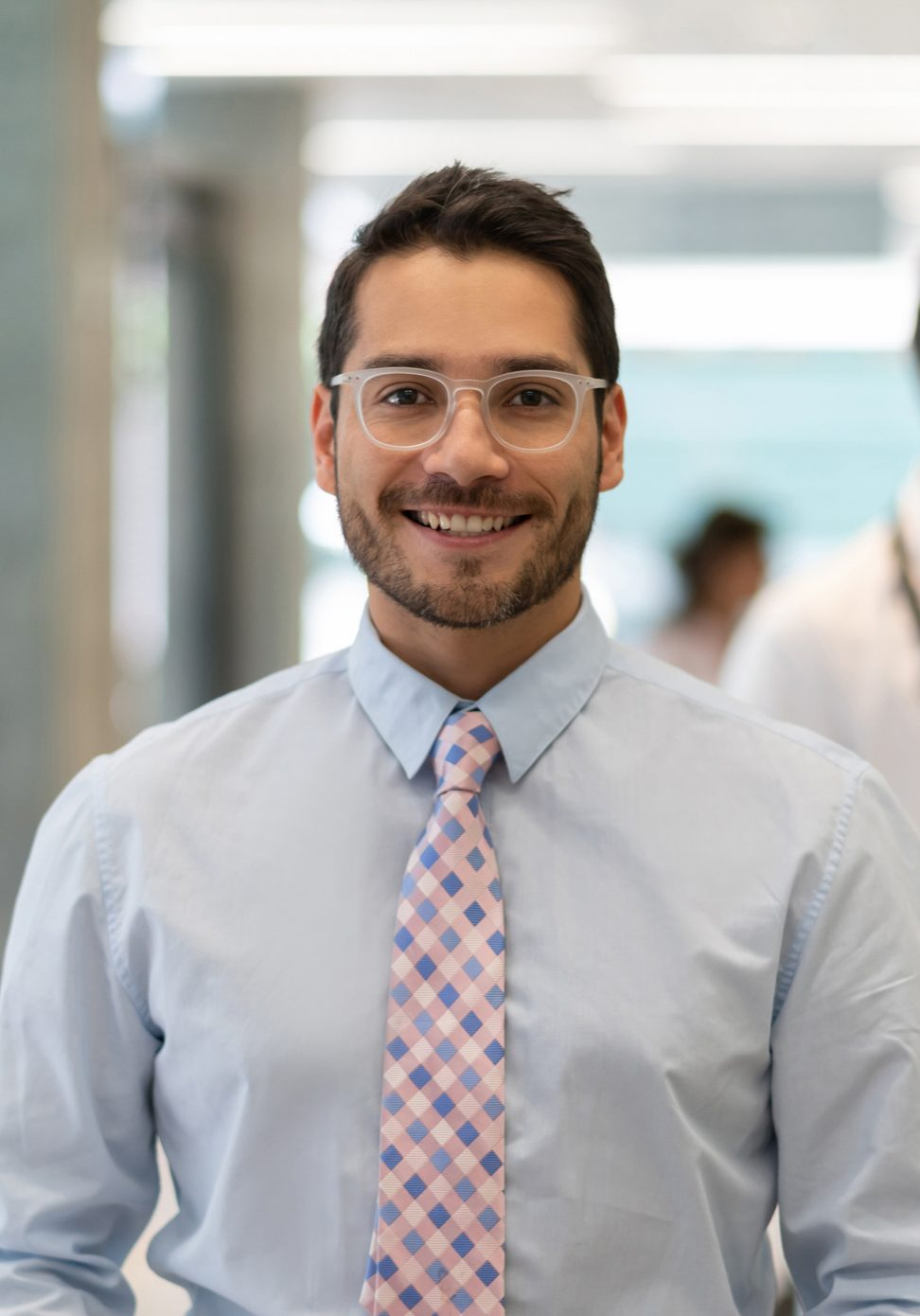 Successful hospital supervisor looking at camera smiling while doctors discuss something at background